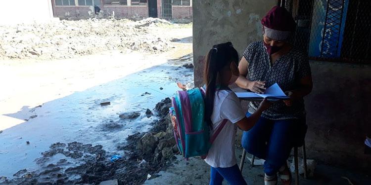 Con lodo al tobillo dejado por las inundaciones y los desechos que arrastraron las aguas, atiende a sus alumnos.