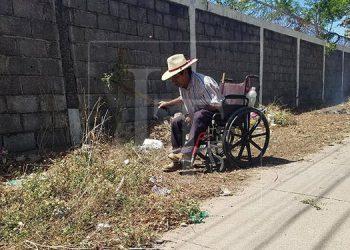 En silla de rueda se moviliza don Santos Álvarez López para hacer labores de limpieza en varios lugares de la ciudad de Choluteca.
