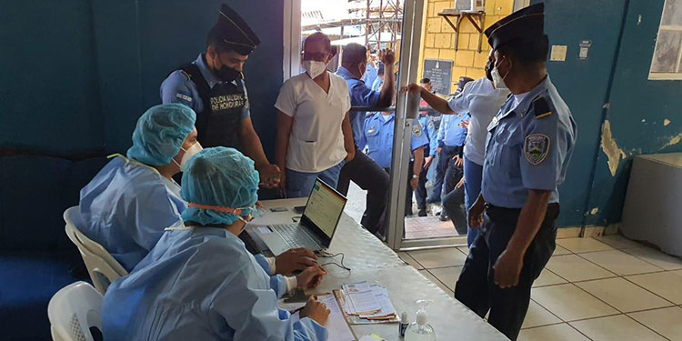 Los funcionarios policiales (foto inserta) reciben la primera dosis de la vacuna de AstraZeneca contra el COVID-19.