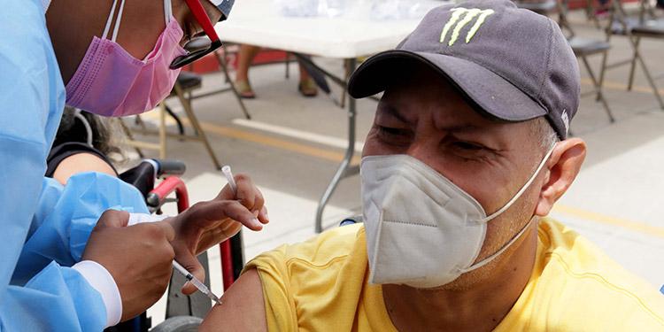 Blas Raudales también fue vacunado en su silla de ruedas en la UNAH e indicó que desde 1982 tiene una discapacidad física.