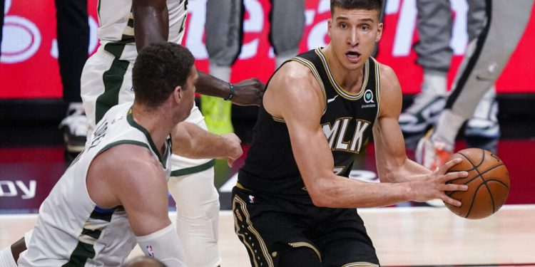 Atlanta Hawks' Bogdan Bogdanovic (13) looks to pass the ball as Milwaukee Bucks' Brook Lopez (11) defends during the first half of Game 4 of the NBA basketball Eastern Conference finals Tuesday, June 29, 2021, in Atlanta. (AP Photo/Brynn Anderson)