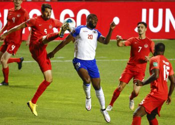 Canada's Steven Vitoria (5) kicks the ball next to Haiti's Frantzdy Pierrot (20) during the second half of a World Cup qualifying soccer match Tuesday, June 15, 2021, in Bridgeview, Ill. (AP Photo/Kamil Krzaczynski)