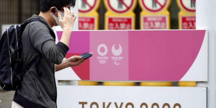Un hombre, con mascarilla para frenar la propagación del coronavirus, pasa junto a un anuncio de los Juegos Olímpicos y Paralímpicos de Tokio 2020, el 29 de junio de 2021, en Tokio. (AP Foto/Eugene Hoshiko)