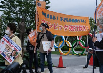 People take part in a protest against the hosting of the 2020 Tokyo Olympic Games in front of the headquarters building of the Japanese Olympic Committee in Tokyo on May 18, 2021. (Photo by Kazuhiro NOGI / AFP)