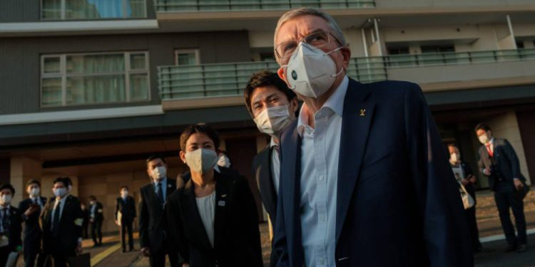 International Olympic Committee president Thomas Bach (R), wearing a face mask, talks to journalists during a visit to the Olympic and Paralympic villages in Tokyo on November 17, 2020, while on a three-day visit to the Japanese capital to discuss the upcoming 2020 Olympic Games postponed until this summer. (Photo by Nicolas Datiche / POOL / AFP)