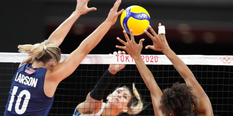 United States' Jordan Larson, left, and United States' Haleigh Washington, right, block a spike by Argentina's Julieta Constanza Lazcano during the women's volleyball preliminary round pool B match between United States and Argentina at the 2020 Summer Olympics, Sunday, July 25, 2021, in Tokyo, Japan. (AP Photo/Frank Augstein)