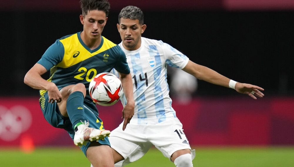 Australia's Lachlan Wales controls the ball challenged by Argentina's Facundo Medina during a men's soccer match at the 2020 Summer Olympics, Thursday, July 22, 2021, in Sapporo, Japan. (AP Photo/SIlvia Izquierdo)