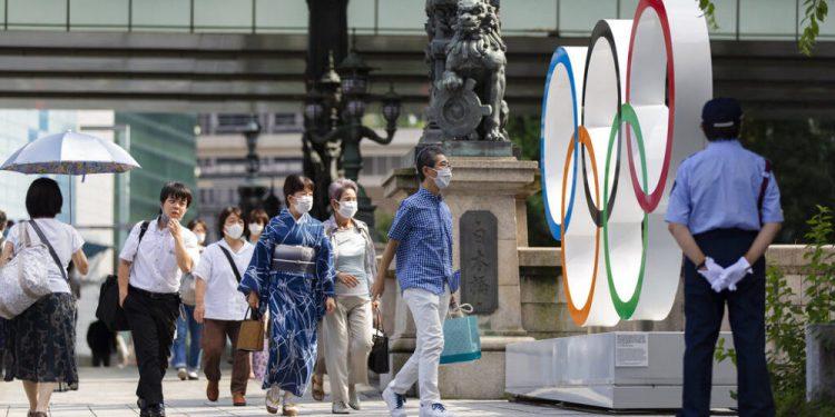 Peatones frente a los anillos olímpicos instalados en en el puente Nippon Bashi en Tokio, el jueves 15 de julio de 2021. (AP Foto/Hiro Komae)
