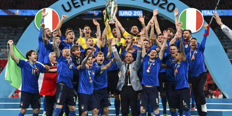 Italy's team celebrates with the trophy on the podium after winning the Euro 2020 soccer championship final between England and Italy at Wembley stadium in London, Sunday, July 11, 2021. (Michael Regan/Pool via AP)
