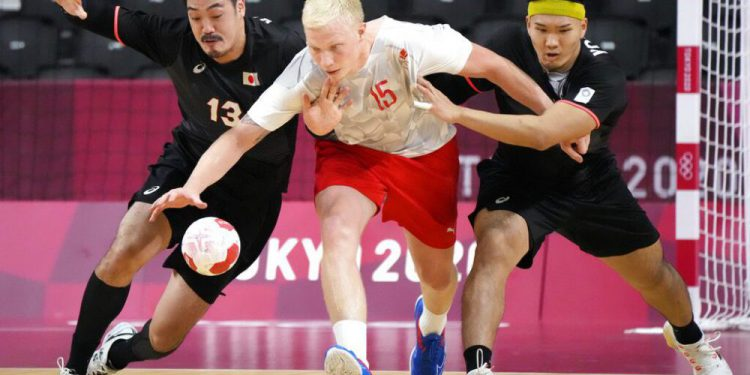 Japan's Kenya Kasahara, left, Japan's Shuichi Yoshida, right, challenge for the ball with Denmark's Magnus Saugstrup during the men's preliminary round group A handball match between Denmark and Japan at the 2020 Summer Olympics, Saturday, July 24, 2021, in Tokyo, Japan. (AP Photo/Sergei Grits)