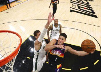 El base de los Suns de Phoenix Devin Booker (1) intenta encestar ante el pivote Brook Lopez, de los Bucks de Milwaukee, en el quinto partido de las Finales de la NBA el sábado 17 de julio de 2021, en Phoenix. (Mark J. Rebilas/Pool Photo vía AP)