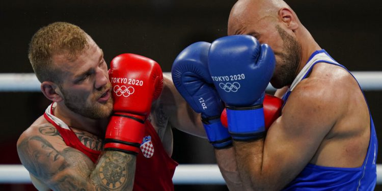 Croatia's Luka Plantic, left, exchanges punches with Jordan's Odai Riyad Adei Alhindawi during their men's light heavyweight 81-kg boxing match at the 2020 Summer Olympics, Sunday, July 25, 2021, in Tokyo, Japan. (AP Photo/Frank Franklin II)