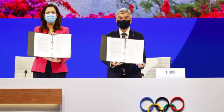 The Honourable Annastacia Palaszczuk MP, Premier of Queensland and Minister for Trade, left, and President of the International Olympic Committee Thomas Bach hold up copies of the Host Agreement after Brisbane was announced as the 2032 Summer Olympics host city during the IOC Session at Hotel Okura in Tokyo, Wednesday, July 21, 2021. (Toru Hanai/Pool Photo via AP)