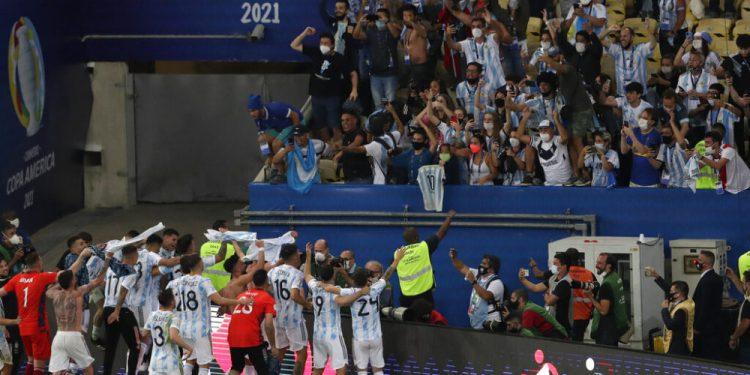 Los jugadores de Argentina celebran con fanáticos tras vencer 1-0 a Brasil en la final de la Copa América, el sábado 10 de julio de 2021, en Río de Janeiro. (AP Foto/Silvia Izquierdo)