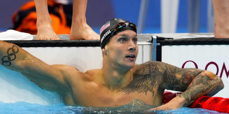 Caeleb Dressel, of United States, looks at the board after finishing a mixed 4x100-meter medley relayat the 2020 Summer Olympics, Saturday, July 31, 2021, in Tokyo, Japan. (AP Photo/Jae C. Hong)