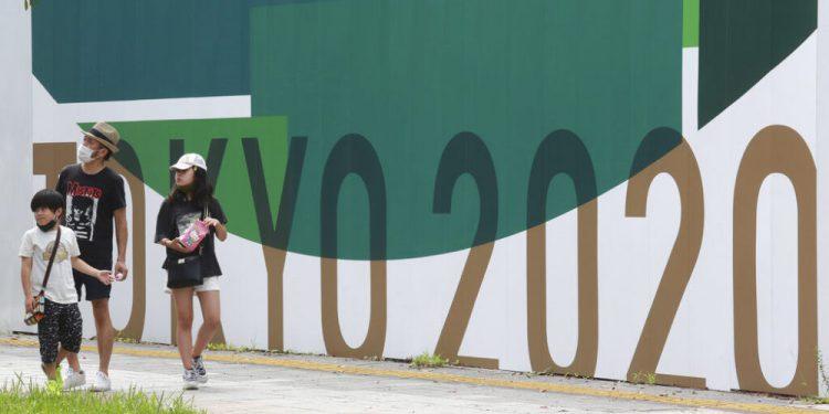 Tres personas pasan junto a carteles de promoción de los Juegos Olímpicos de Tokio 2020, en Tokio, el 14 de julio de 2021. (AP Foto/Koji Sasahara)