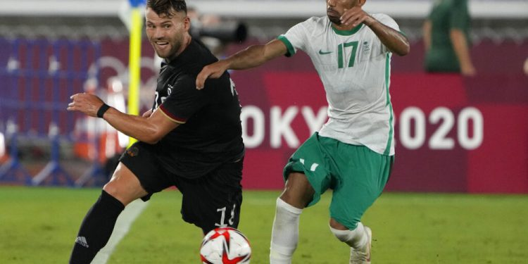 Germany's Eduard Loewen, left, and Saudi Arabia's Ayman Alkhulaif battle for the ball during a men's soccer match at the 2020 Summer Olympics, Sunday, July 25, 2021, in Yokohama, Japan. (AP Photo/Kiichiro Sato)