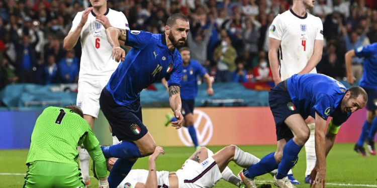 Italy's Leonardo Bonucci, center, runs to celebrate after scoring his sides first goal during the Euro 2020 soccer championship final match between England and Italy at Wembley Stadium in London, Sunday, July 11, 2021. (Paul Ellis/Pool via AP)
