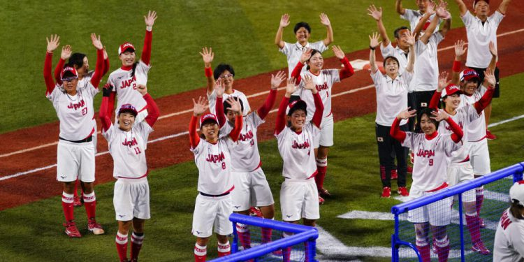 Members of team Japan wave to the audience after a a softball game against the United States at the 2020 Summer Olympics, Tuesday, July 27, 2021, in Yokohama, Japan. Japan won 2-0. (AP Photo/Matt Slocum)