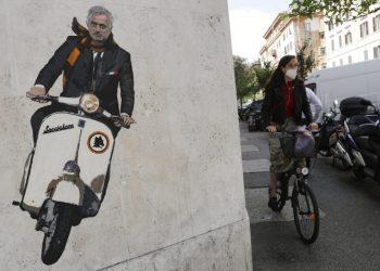 """Una mujer en bicicleta pasa junto a un cartel que muestra a José Mourinho en una motoneta en Roma el 7 de mayo del 2021. Mourinho, quien hace poco llegó a los entrenamientos de Roma en una Vespa, se mostró sonriente y tal vez menos combativo que de costumbre en su primera conferencia de prensa como técnico """"giallorosso"""" el 8 de julio del 2021. (AP Photo/Gregorio Borgia)"""