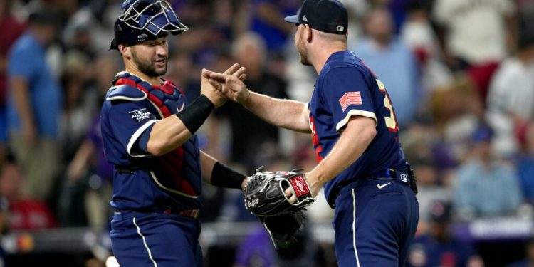 American League's Liam Hendriks, of the Chicago White Sox, right, greets catcher Marcus Semien, of the Toronto Blue Jays, after the MLB All-Star baseball game, Tuesday, July 13, 2021, in Denver. The American League defeated the National League 5-2. (AP Photo/David Zalubowski)