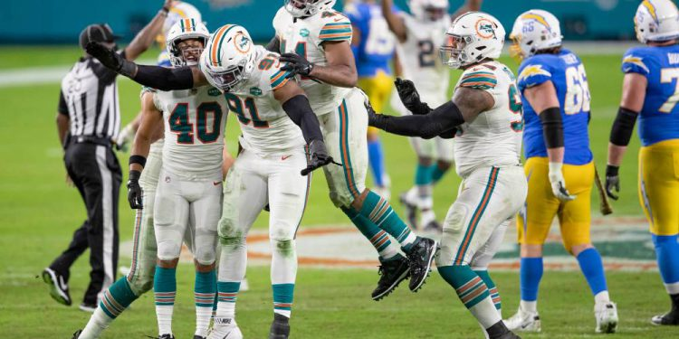 Miami Dolphins defensive end Emmanuel Ogbah (91) celebrates after tipping a pass attempted by Los Angeles Chargers quarterback Justin Herbert (10) on fourth down and one at Hard Rock Stadium in Miami Gardens, November 15, 2020. Dolphins took over on downs. (ALLEN EYESTONE / THE PALM BEACH POST)