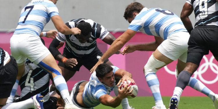 Argentina's Lucio Cinti, center, secures the ball, in Argentina's men's rugby sevens semifinal match against Fiji at the 2020 Summer Olympics, Wednesday, July 28, 2021 in Tokyo, Japan. (AP Photo/Shuji Kajiyama)