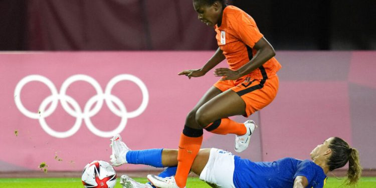 Netherlands' Lineth Beerensteyn leaps over Brazil's Tamires during a women's soccer match at the 2020 Summer Olympics, Saturday, July 24, 2021, in Miyagi, Japan. (AP Photo/Andre Penner)