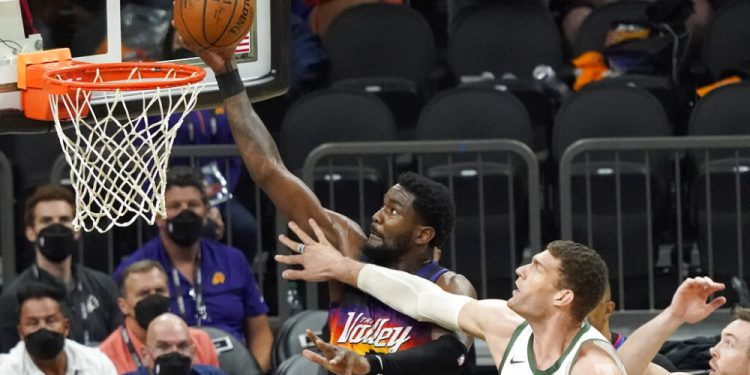 Phoenix Suns center Deandre Ayton (22) shoots against Milwaukee Bucks center Brook Lopez (11) during the second half of Game 2 of basketball's NBA Finals, Thursday, July 8, 2021, in Phoenix. (AP Photo/Matt York)