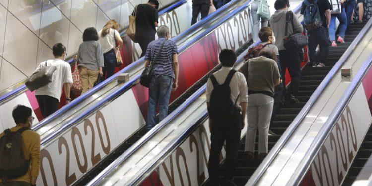 Personas ascienden por elevadores con logos de los Juegos Olímpicos de Tokio, el martes 6 de julio de 2021. (AP Foto/Koji Sasahara)
