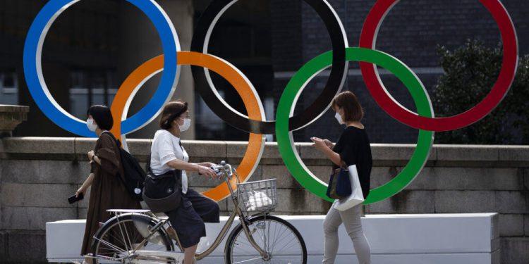 En esta foto del 15 de julio del 2021, transeúntes pasan delante de los anillos olímpicos junto al Puente Nippon Bashi en Tokio. Un pesista de Uganda que escapó durante entrenamientos preolímpicos en Japón la semana pasada fue localizado y está siendo entrevistado por la policía, dijeron las autoridades el 20 de julio. (AP Foto/Hiro Komae)