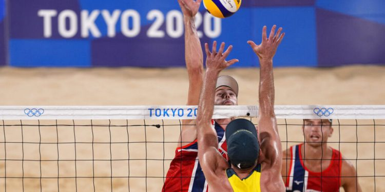 Christopher McHugh, of Australia, blocks against Anders Berntsen Mol, of Norway, during a men's beach volleyball match at the 2020 Summer Olympics, Saturday, July 24, 2021, in Tokyo, Japan. (AP Photo/Petros Giannakouris)