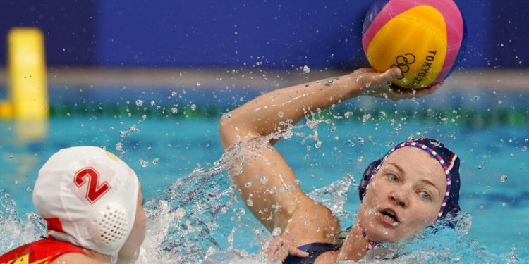 Evgeniya Ivanova, right, of the Russian Olympic Committee, tries to get away from China's Xinyan Wang (2) during a preliminary round women's water polo match at the 2020 Summer Olympics, Saturday, July 24, 2021, in Tokyo, Japan. (AP Photo/Mark Humphrey)