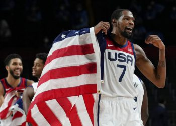 United States' Kevin Durant (7) waves a United States flag as he celebrates with teammates after their win over France in a men's basketball Gold medal game at the 2020 Summer Olympics, Saturday, Aug. 7, 2021, in Saitama, Japan. (AP Photo/Eric Gay)
