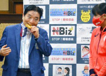 El alcalde de Nagoya, Takashi Kawamura, izquierda, muerde la presea de oro de la lanzadora Miu Goto, derecha, del equipo olímpico japonés de softbol, en el Ayuntamiento de Nagoya, Japón, el miércoles 4 de agosto de 2021. (Kyodo News vía AP)