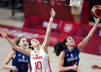 La serbia Sonja Vasic intenta una bandeja ante la defensa de la china Zhenqi Pan durante los cuartos de final del torneo olímpico, el miércoles 4 de agosto de 2021, en Saitama, Japón. (AP Foto/Charlie Neibergall)