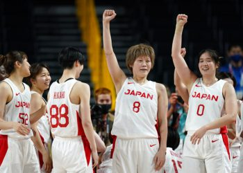 Japan's Maki Takada (8) and Moeko Nagaoka (0) celebrate with teammates at the end of a women's basketball semifinal round game against France at the 2020 Summer Olympics, Friday, Aug. 6, 2021, in Saitama, Japan. (AP Photo/Charlie Neibergall)