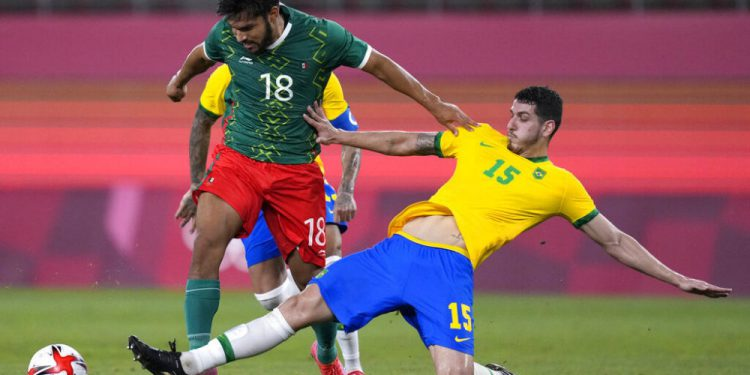 Mexico's Eduardo Aguirre (18) and Brazil's Nino (15) battle for the ball during a men's soccer semifinal match at the 2020 Summer Olympics, Tuesday, Aug. 3, 2021, in Kashima, Japan. (AP Photo/Andre Penner)