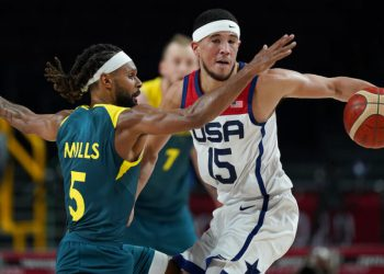 United States's Devin Booker (15) and Australia's Patty Mills (5) fight for the ball during men's basketball semifinal game at the 2020 Summer Olympics, Thursday, Aug. 5, 2021, in Saitama, Japan. (AP Photo/Charlie Neibergall)