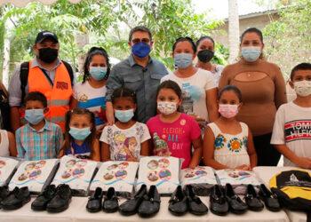El Presidente Juan Orlando Hernández, junto a niños beneficiados con la entrega de kits escolares.