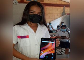 Una niña enseña la tablet que ella y sus compañeros recibieron en la escuela.