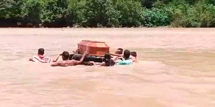 El ataúd con el cuerpo del fallecido, Gerardo Contreras, fue trasladado por el río desde Duyure a Morolica, en el sureño departamento de Choluteca.