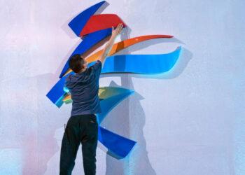 Un miembro del personal salta para reacomodar un logo de los Juegos Olímpicos de Invierno Beijing 2022 antes de una ceremonia de lanzamiento para revelar el lema de los Juegos Olímpicos y Paralímpicos de Invierno, en Beijing, el viernes 17 de septiembre de 2021. (AP Foto/Mark Schiefelbein)